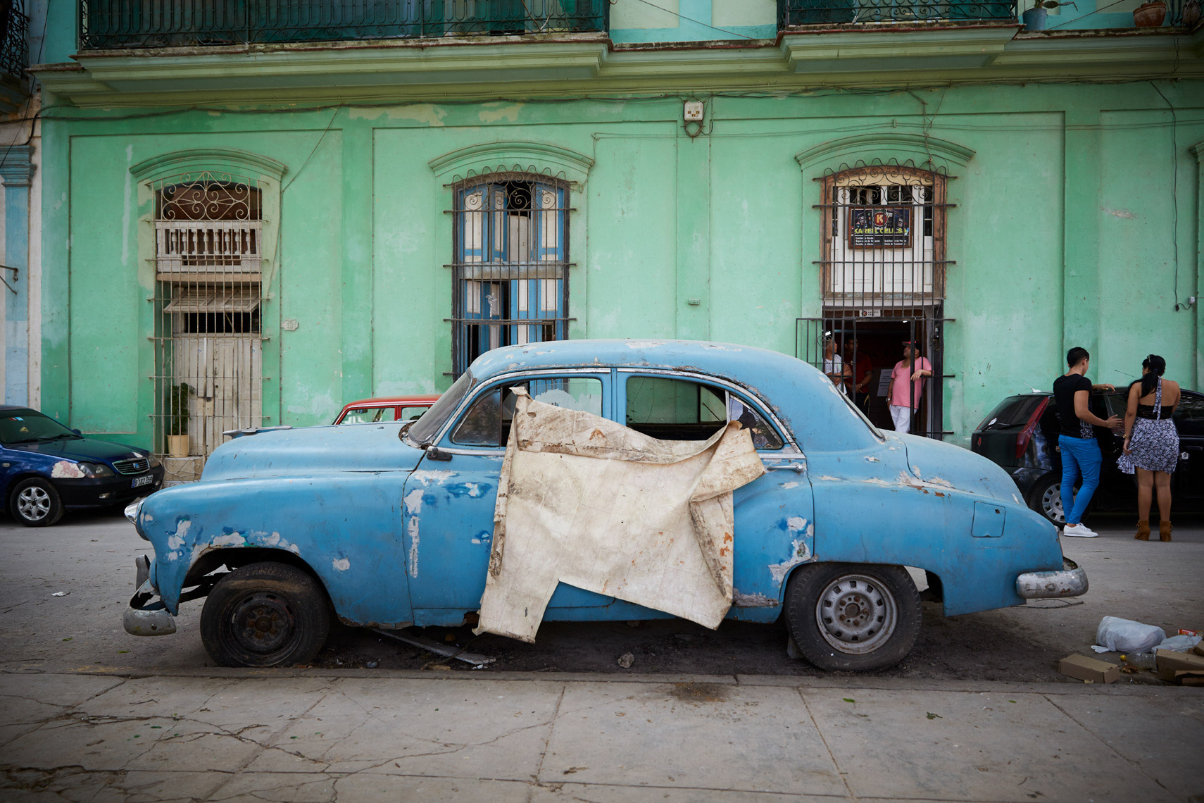 antique blue car in front of teal apartment wall in Cuba