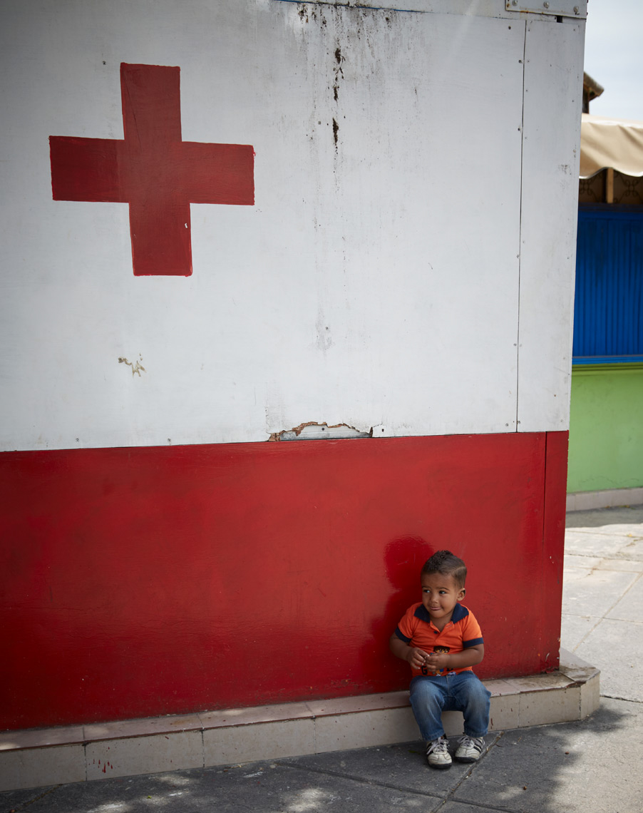 little boy in orange shirt sitting in front of old hospital with red cross on wall