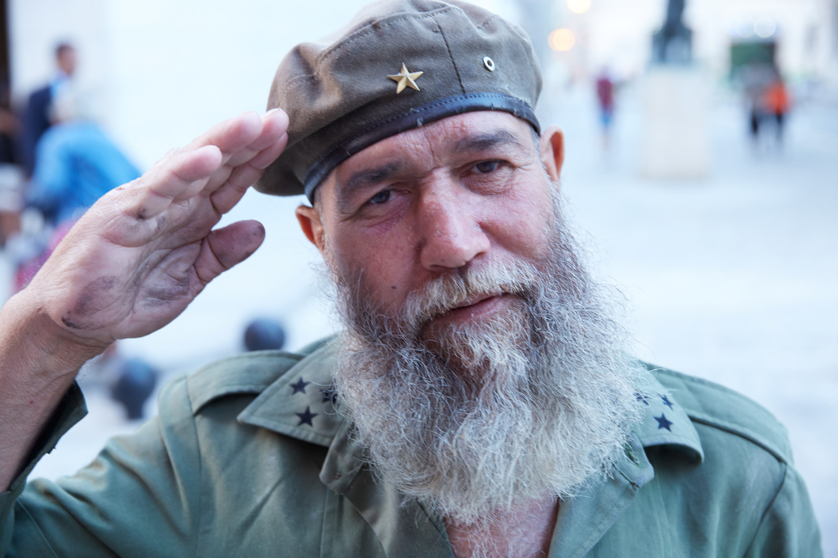 old man wearing Fidel Castro hat saluting camera