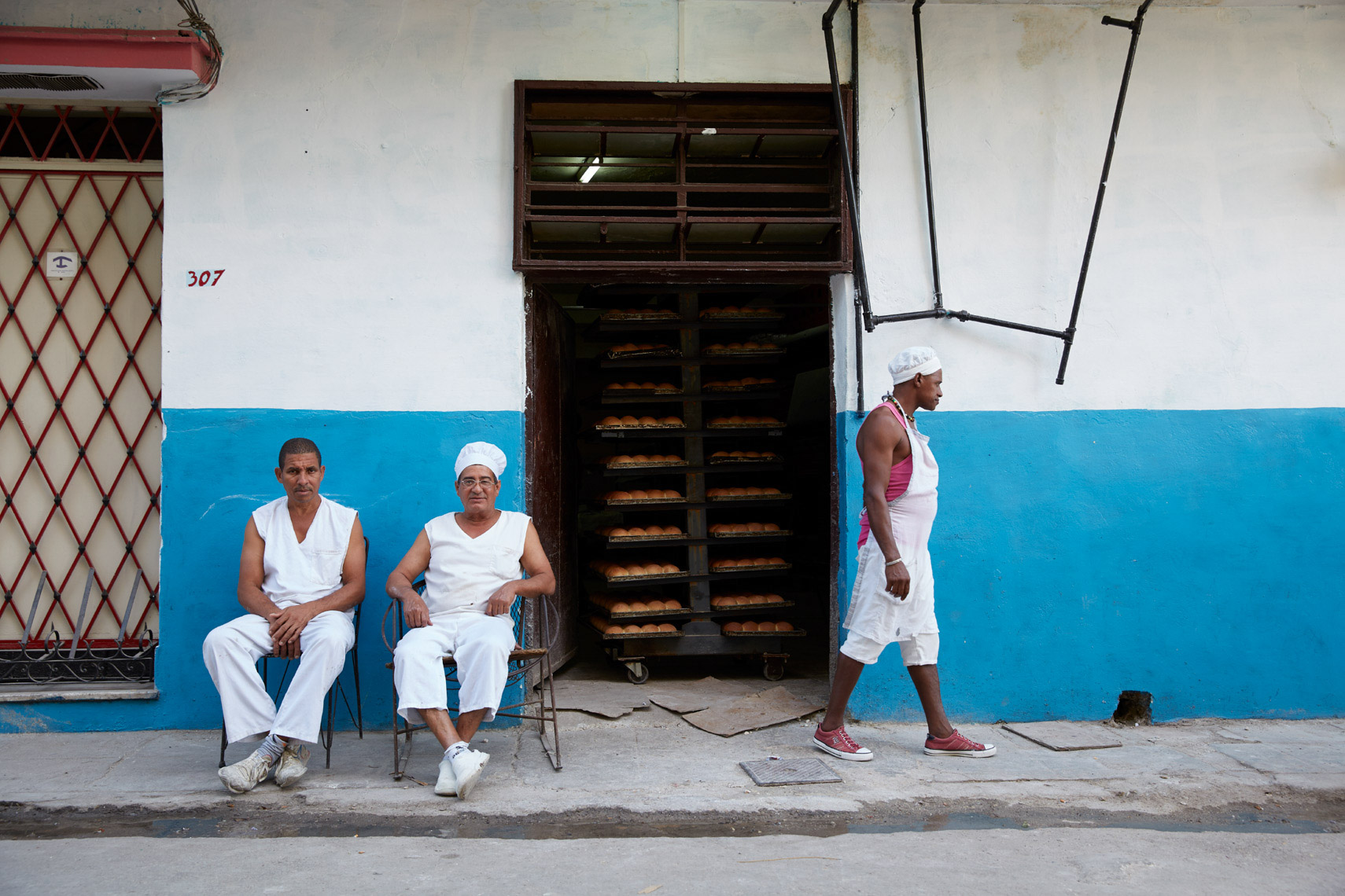 3 chefs outside bakery with white and blue walls in Cuba