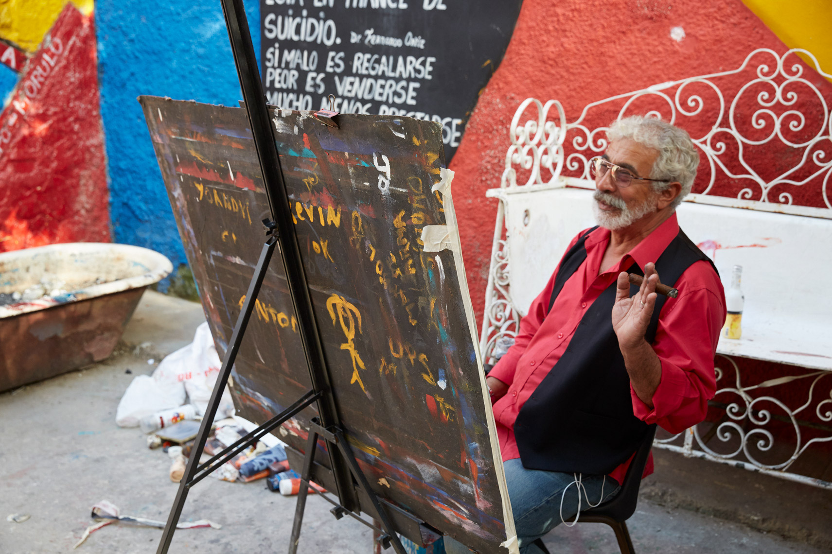 cuban painter smoking cigar in front of easel