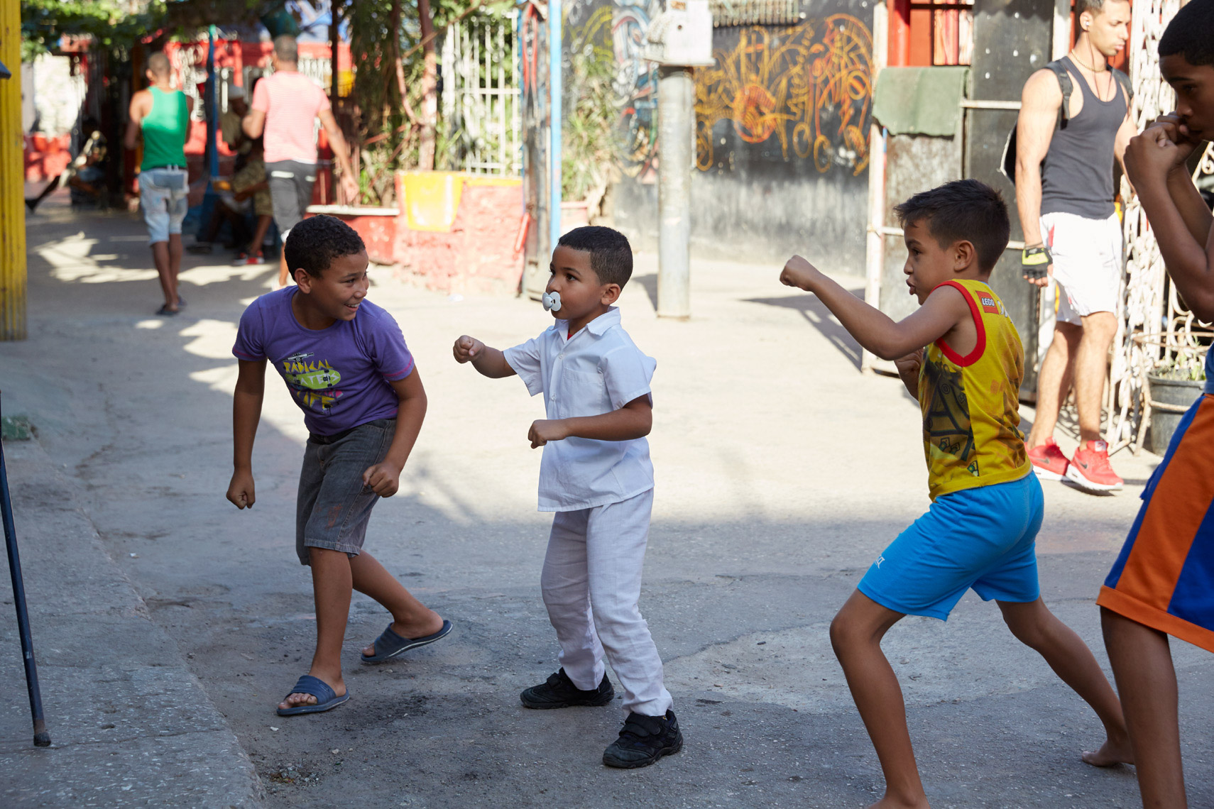 3 kids boxing in colorful alleyway in Cuba