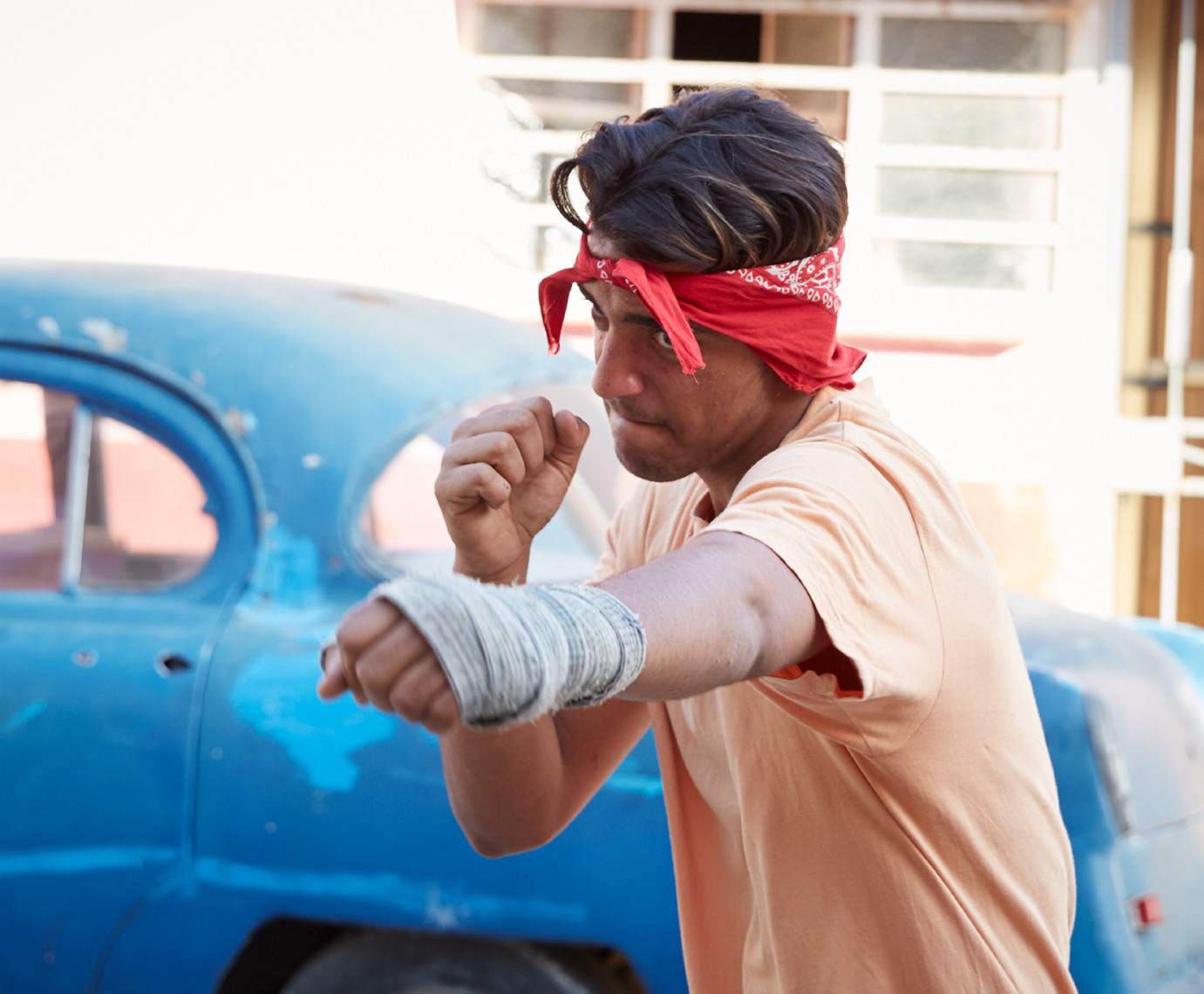 man with red bandana practicing boxing in front of old blue cuban car