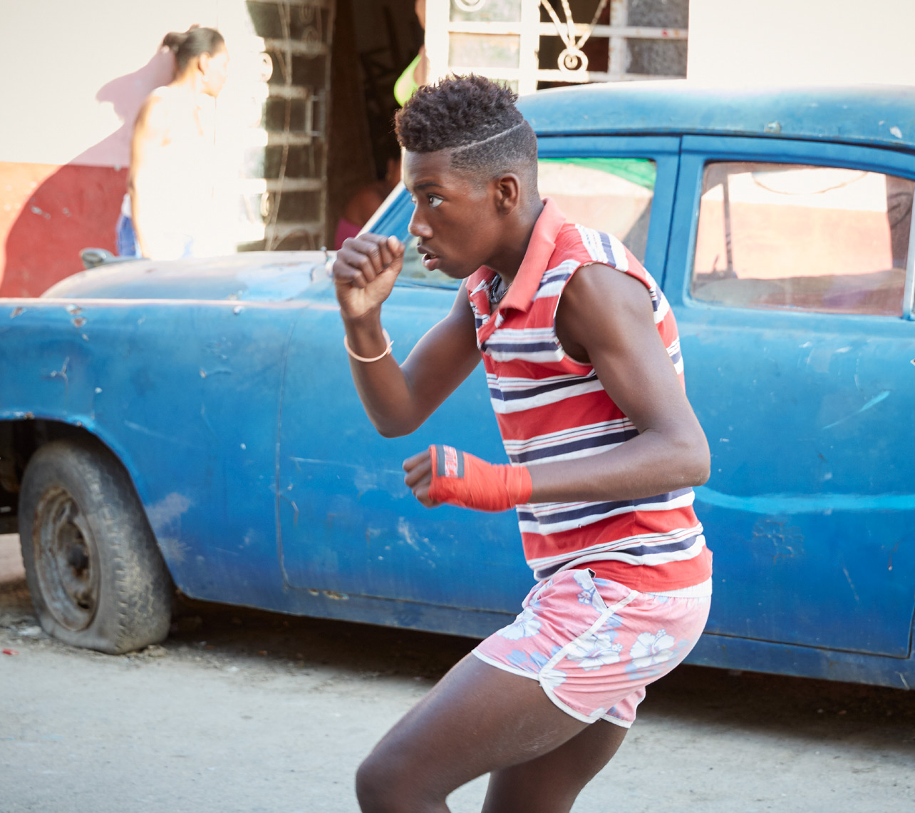 young boy practicing boxing in front of old blue car in Cuba