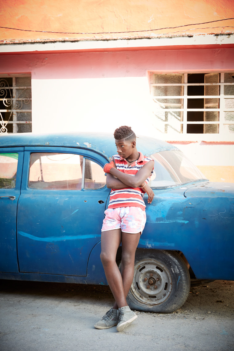 young boy in colorful clothing leaning against old blue car in Cuba