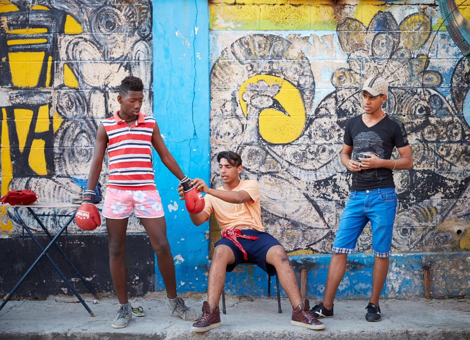 3 young boys practicing boxing in front of an art-deco wall in Cuba