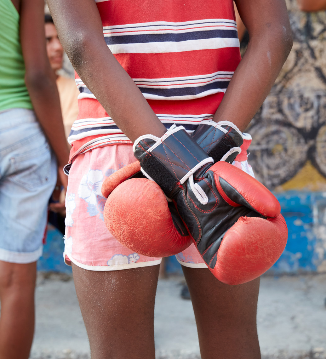 detail of young kid with boxing gloves and colorful clothing in Cuba