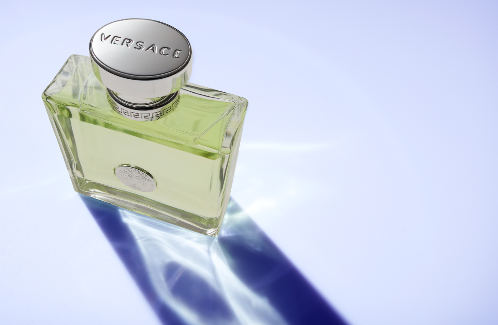 bottle of green perfume with shadow on blue surface