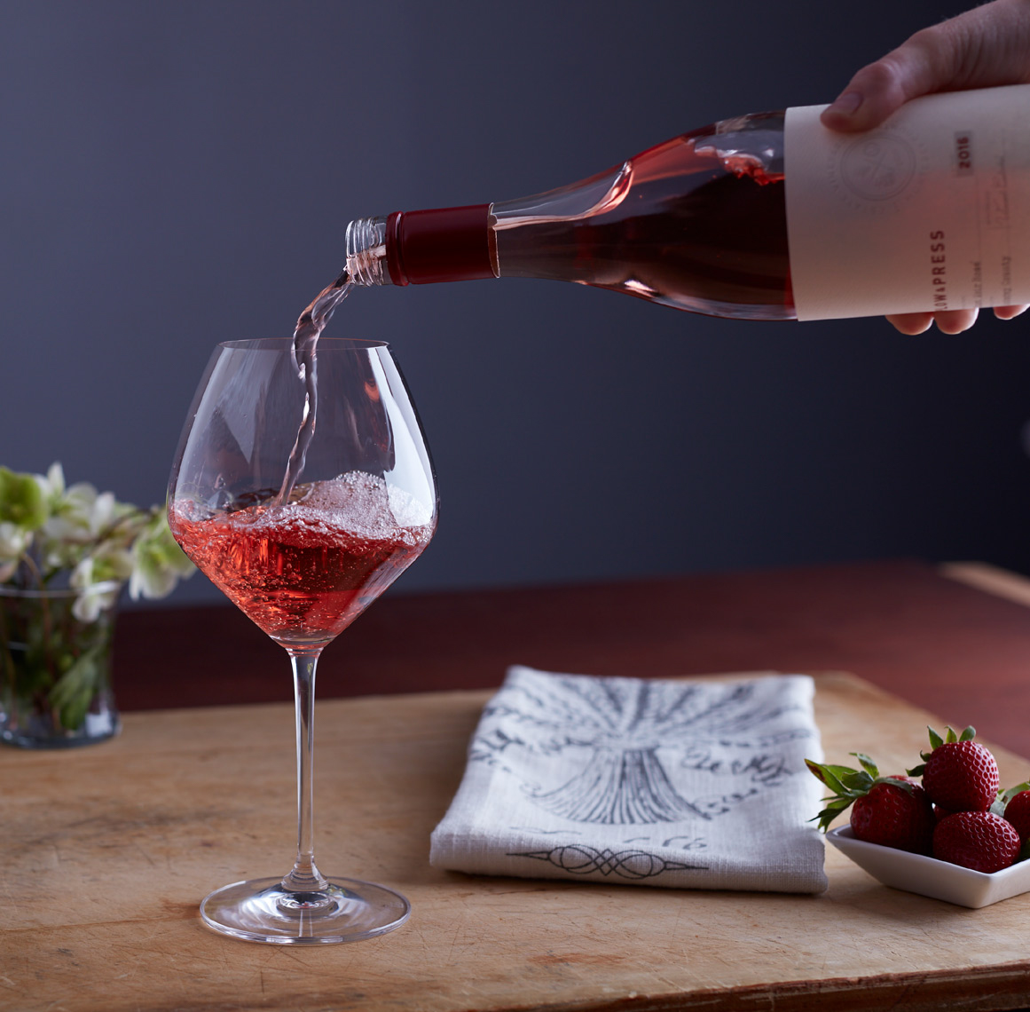 bottle pouring rose wine into a glass with strawberries and a dish towel