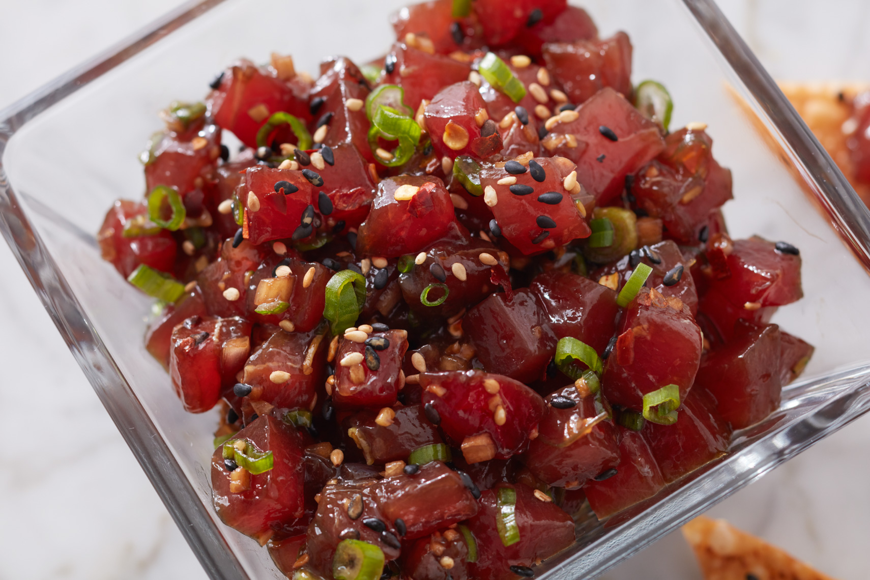tuna poke with shallots and sesame seeds in glass bowl