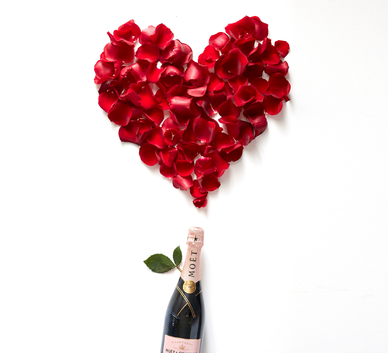 bottle of champagne with rose petals in a heart shape