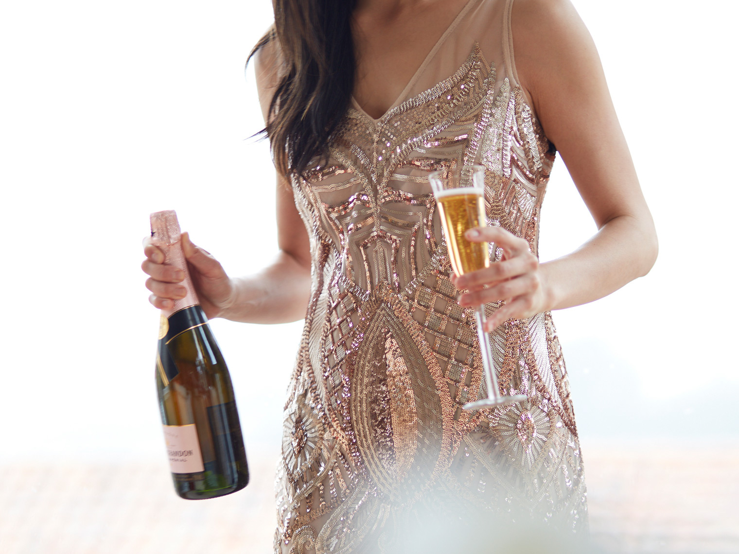 woman in sequin gown holding a bottle and glass of champagne