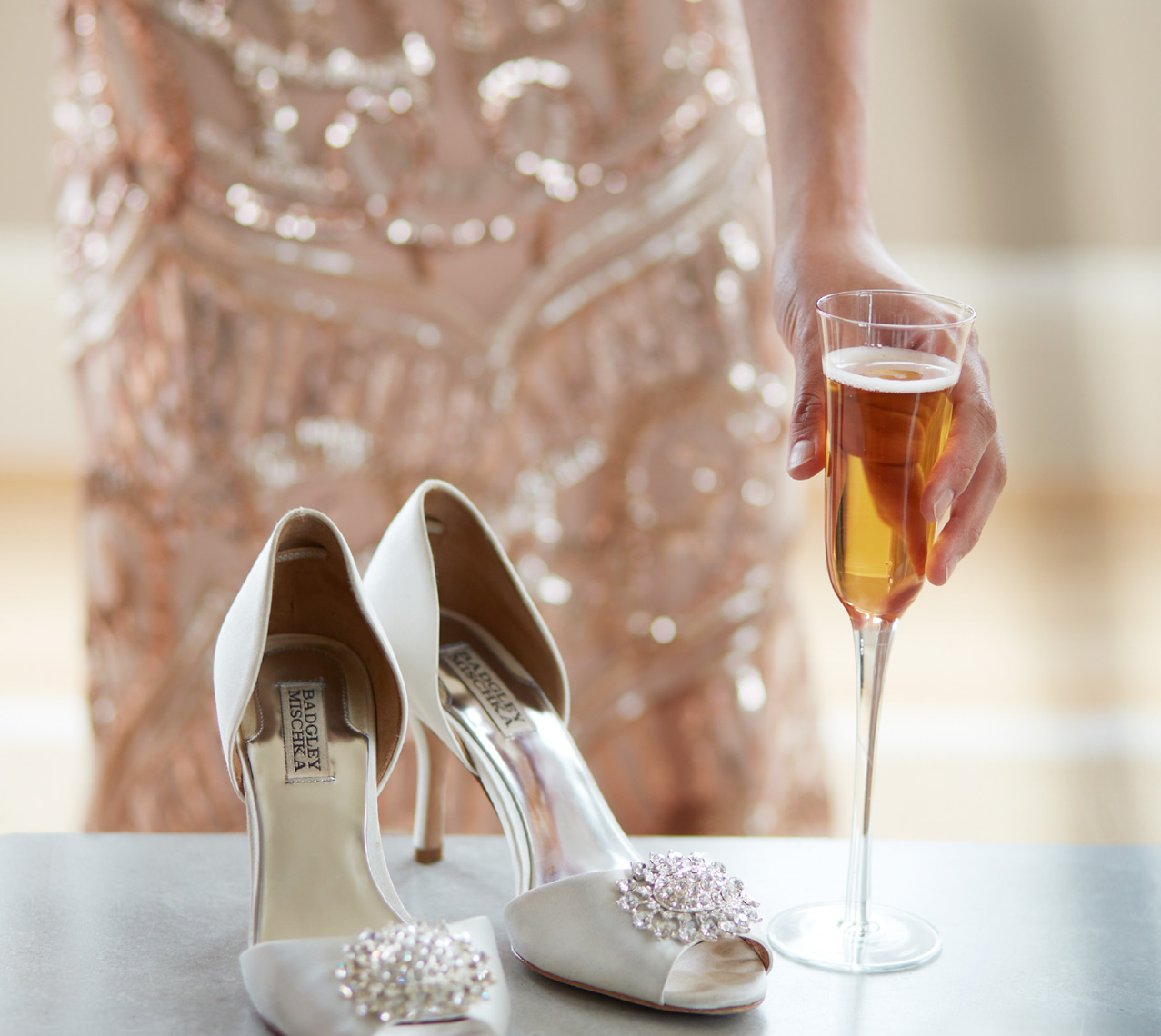 woman in sequin gown holding glass of champagne next to a pair of satin heels