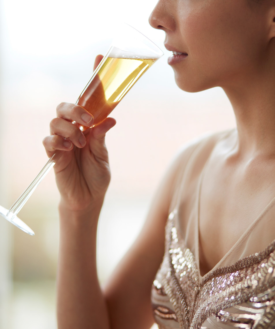 woman in sequin dress holding glass of champagne up to lips