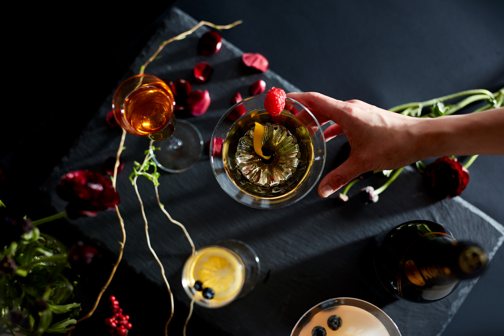 downward view of woman picking up martini with a twist and fresh fruit on clean black surface