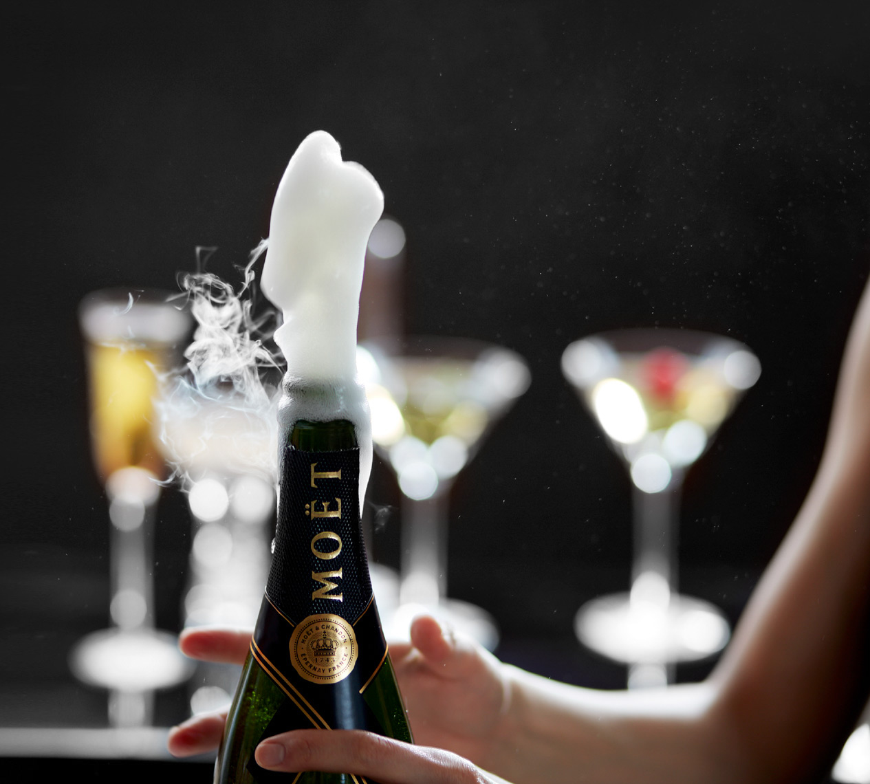 woman popping open a bottle of champagne with martini and champagne glasses