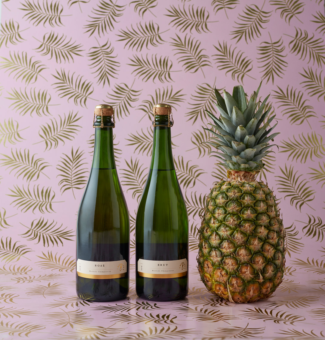 2 bottles of champagne next to pineapple with pink and gold pattern background