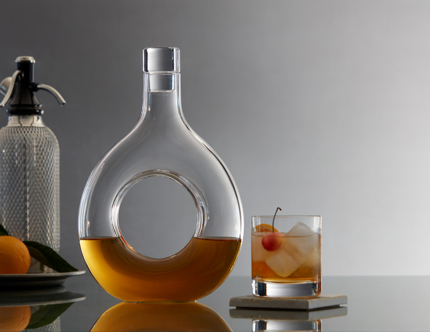 circular decanter next to whiskey on the rocks with a cherry