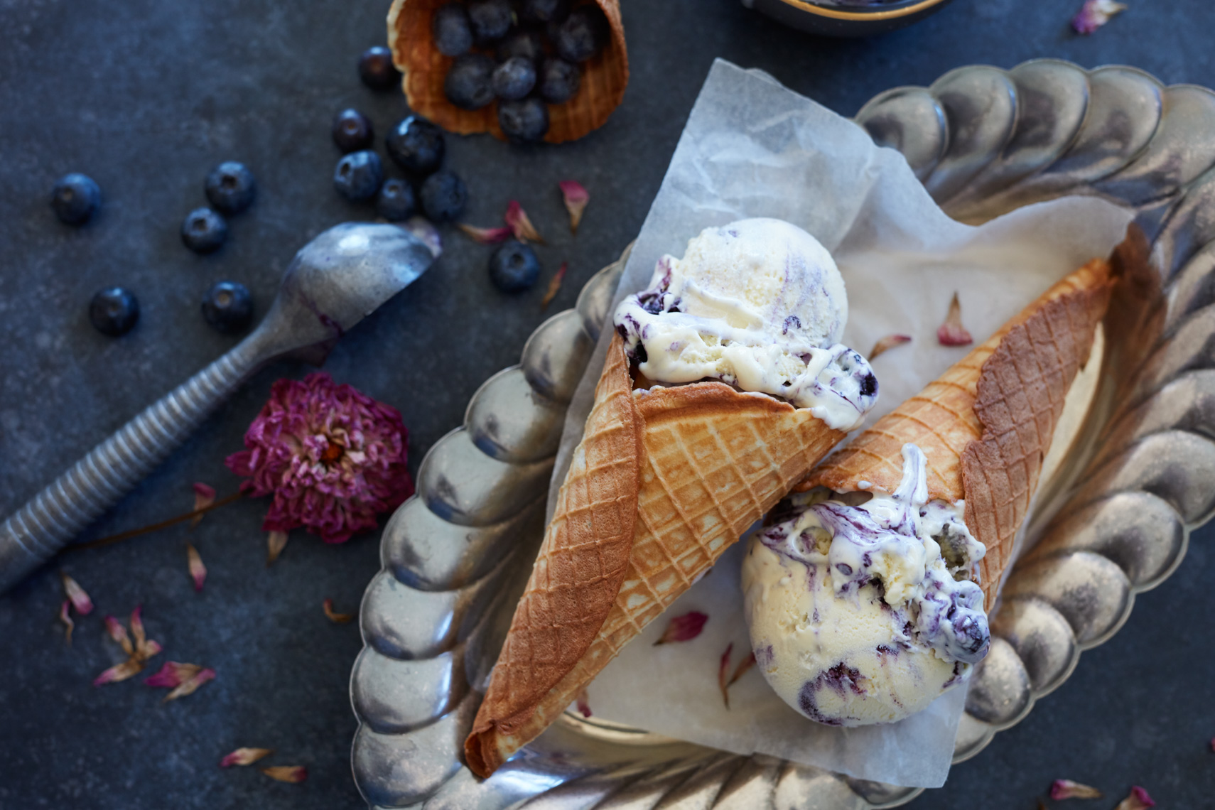 blueberry ice cream in waffle cones on silver tray with ice cream scooper
