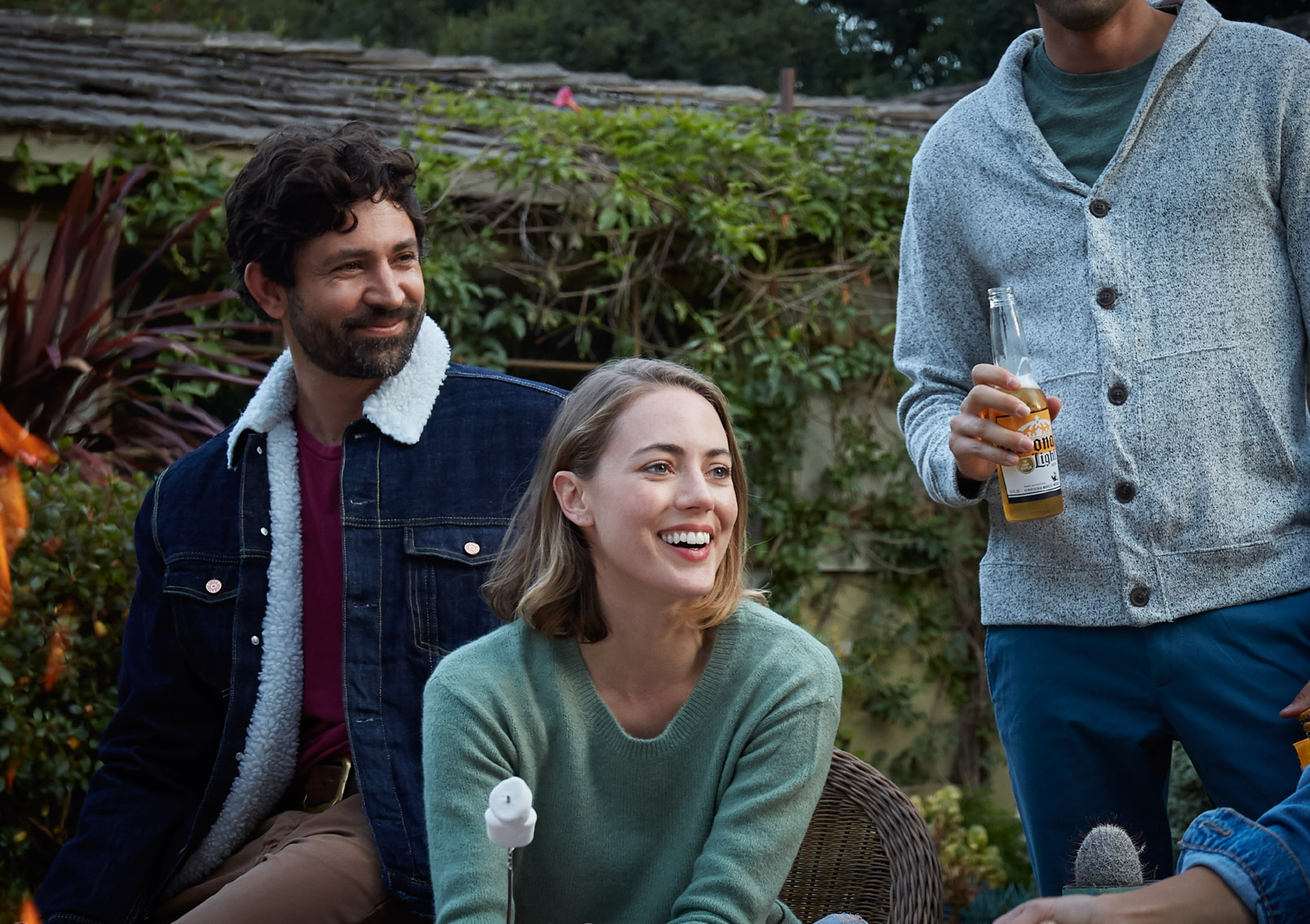 Woman and two men roasting marshmallows and drinking and laughing outside on a fall evening