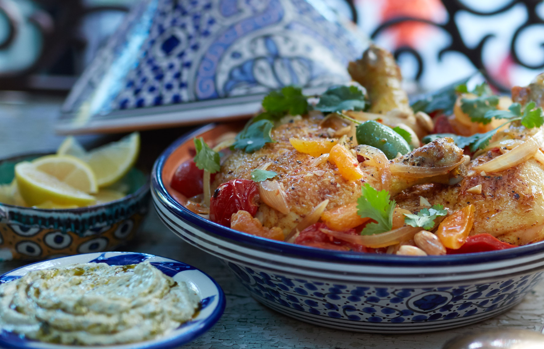 chicken tagine on blue moroccan bowl with lemon and hummus