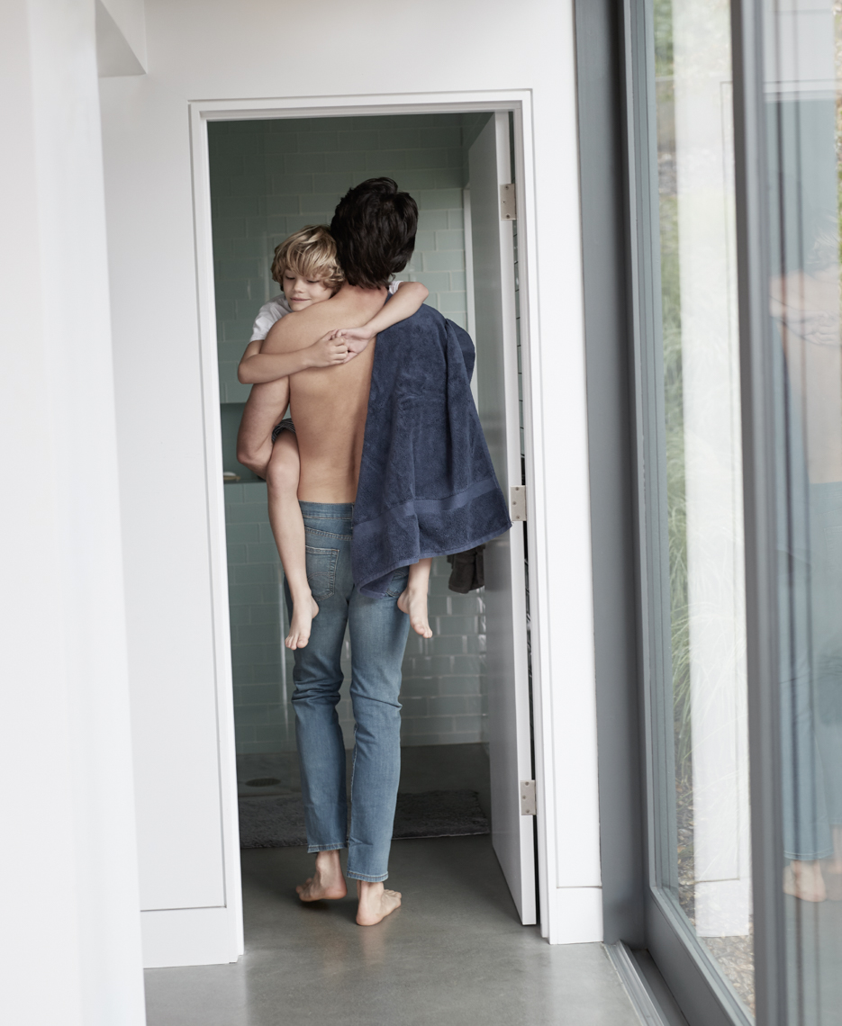 Shirtless dad in jeans seen from behind carrying his sleeping boy into the bathroom