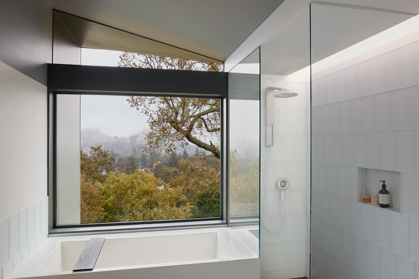 bathroom in modern-art house with white tiles and white bathtub and window view of forest during fall
