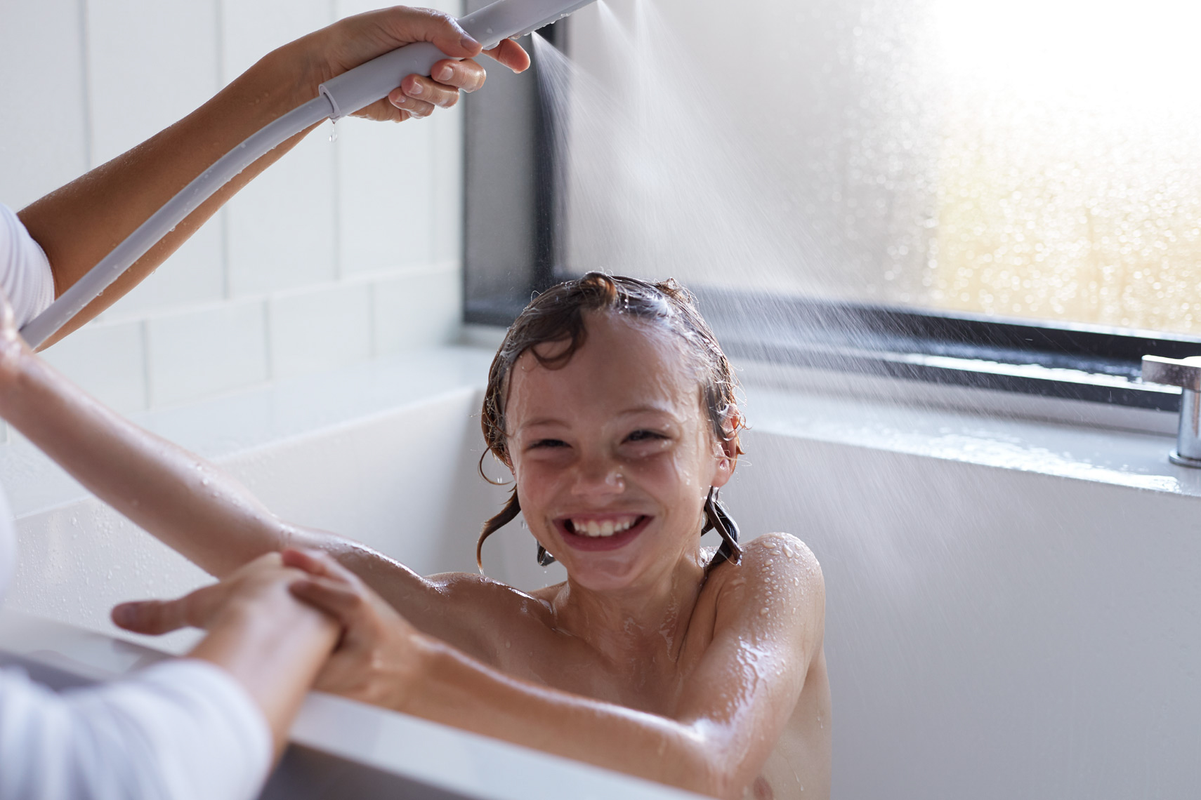 young kid in white bathtub with mom spraying with shower hose