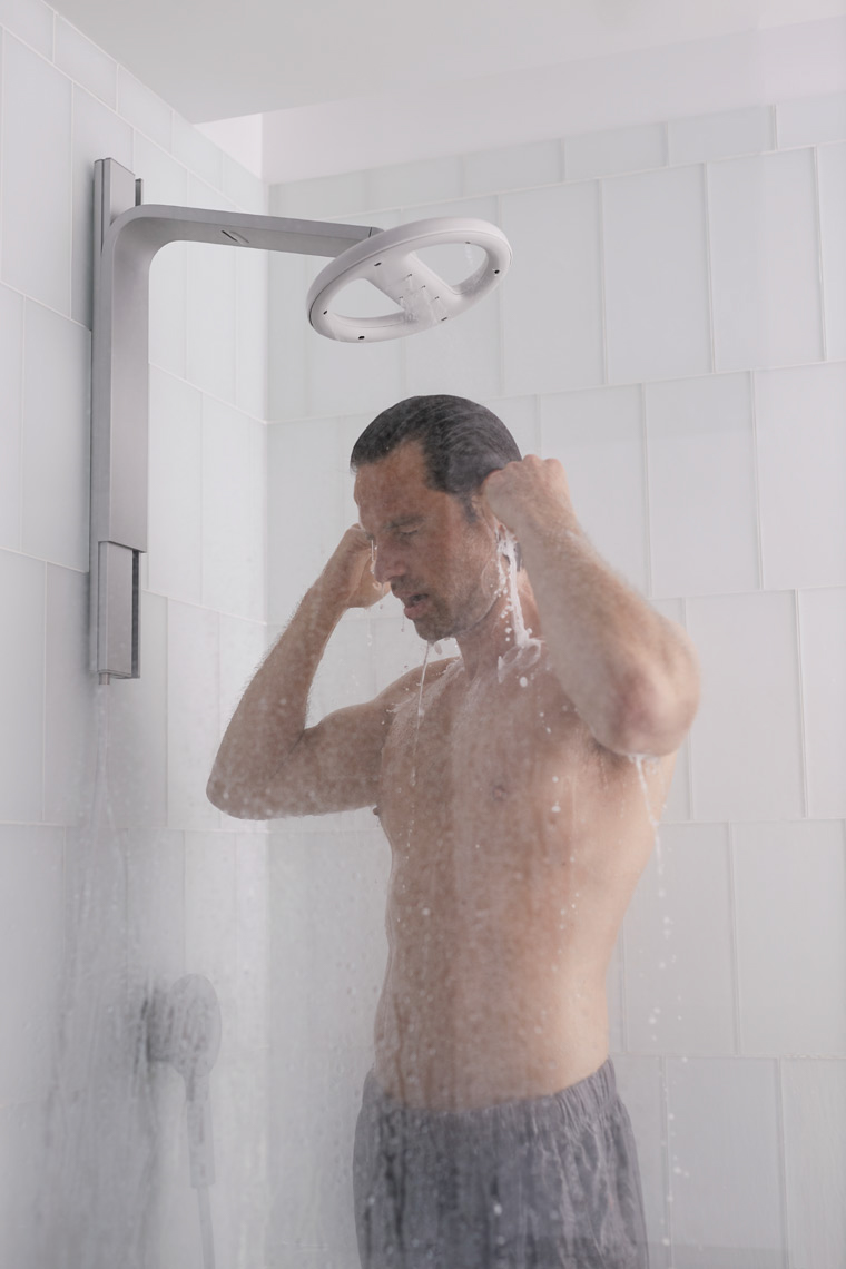man with grey shorts in running shower with glass door