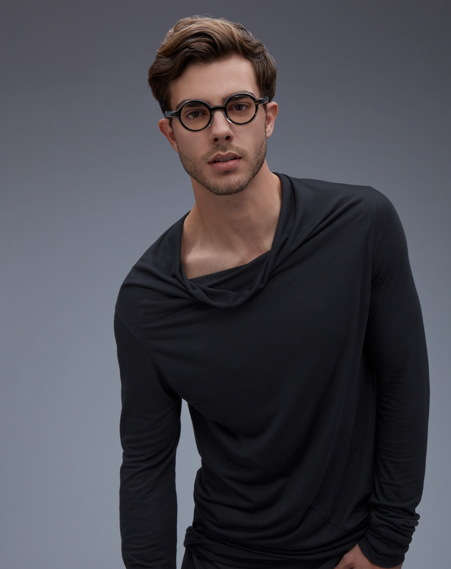 man wearing loose grey shirt and small circular frames