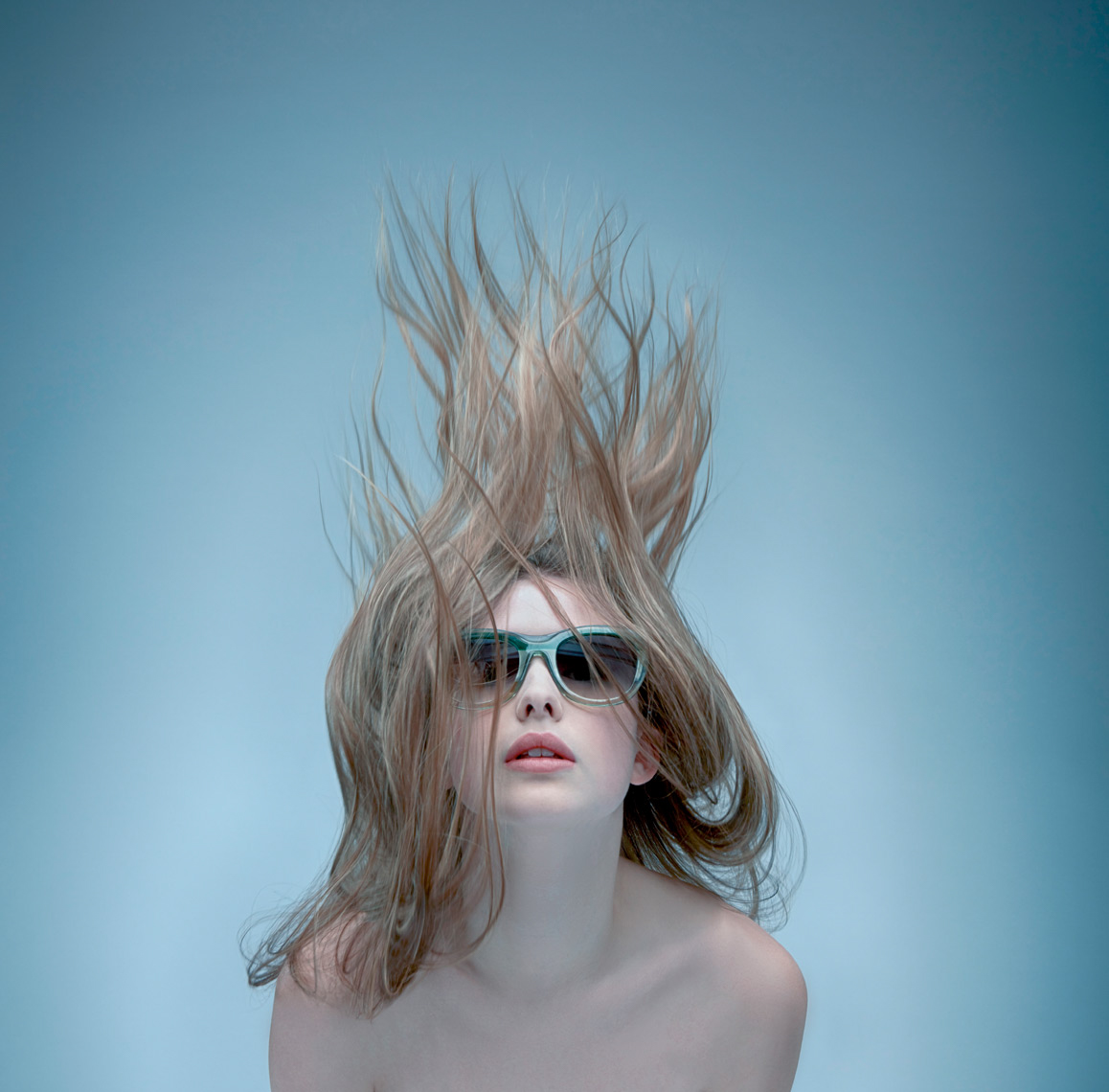 woman with dark shades and blue frames with hair blown up above her face