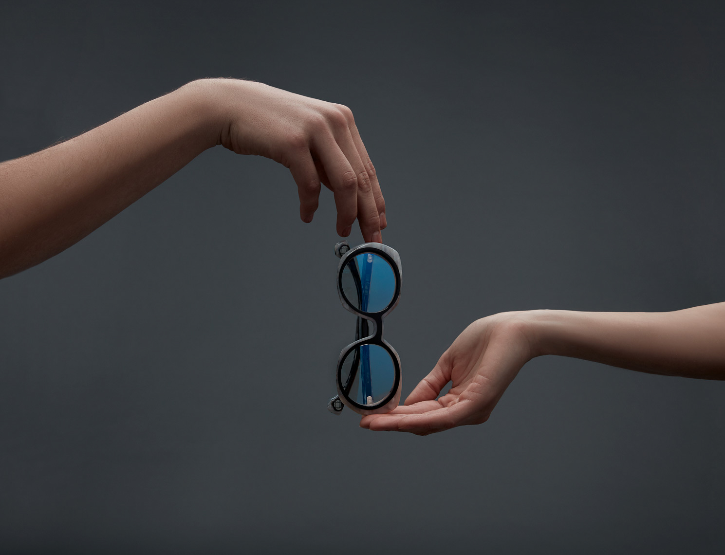 two hands holding circular tinted glasses