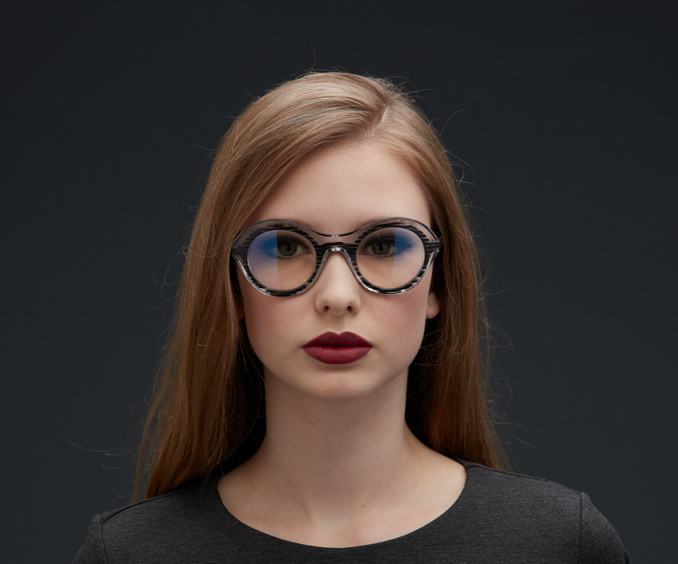 woman looking straight at camera wearing dark patterned lenses