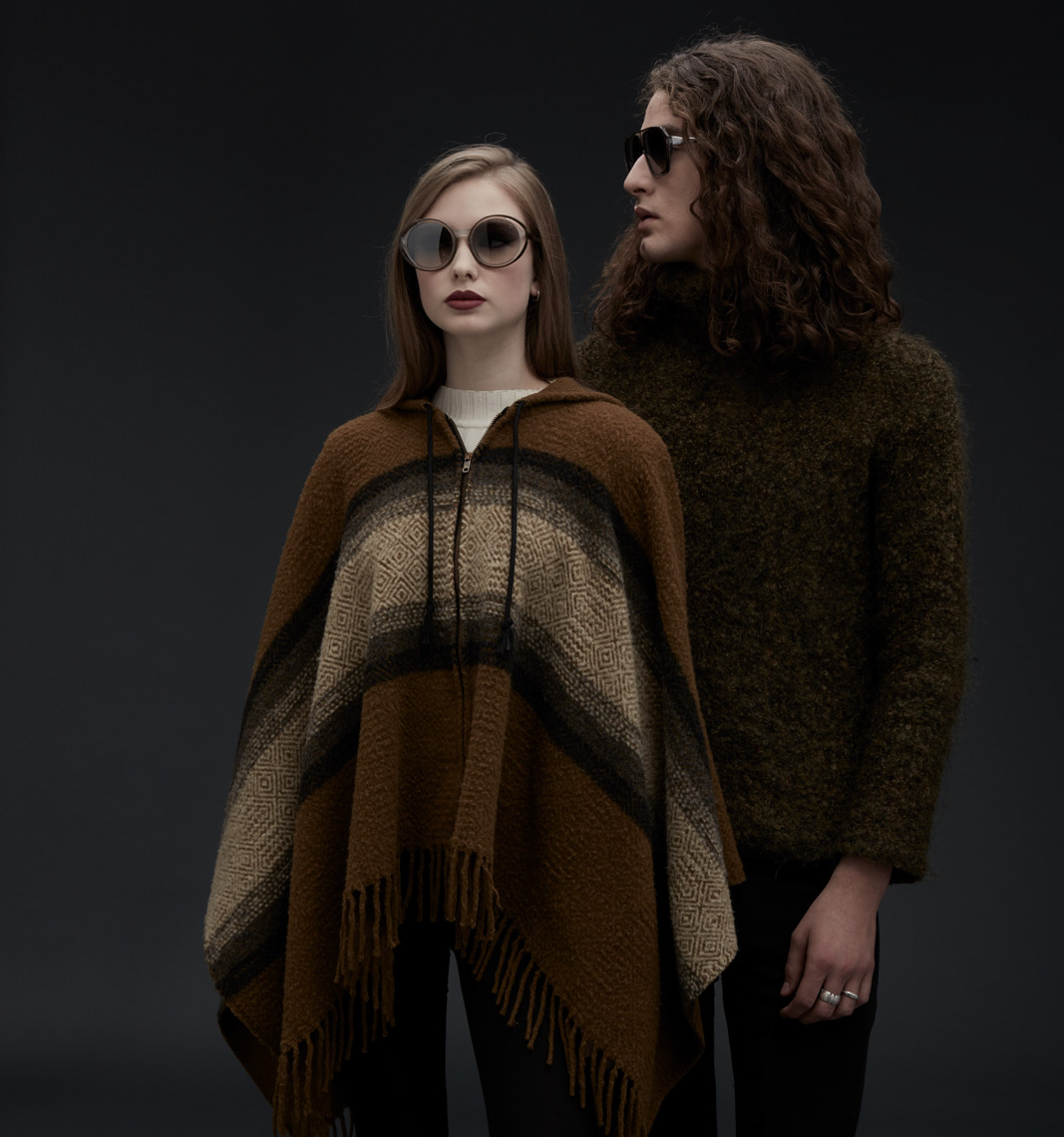curly haired model wearing wool sweater and glasses looking at straight haired model wearing circular frames