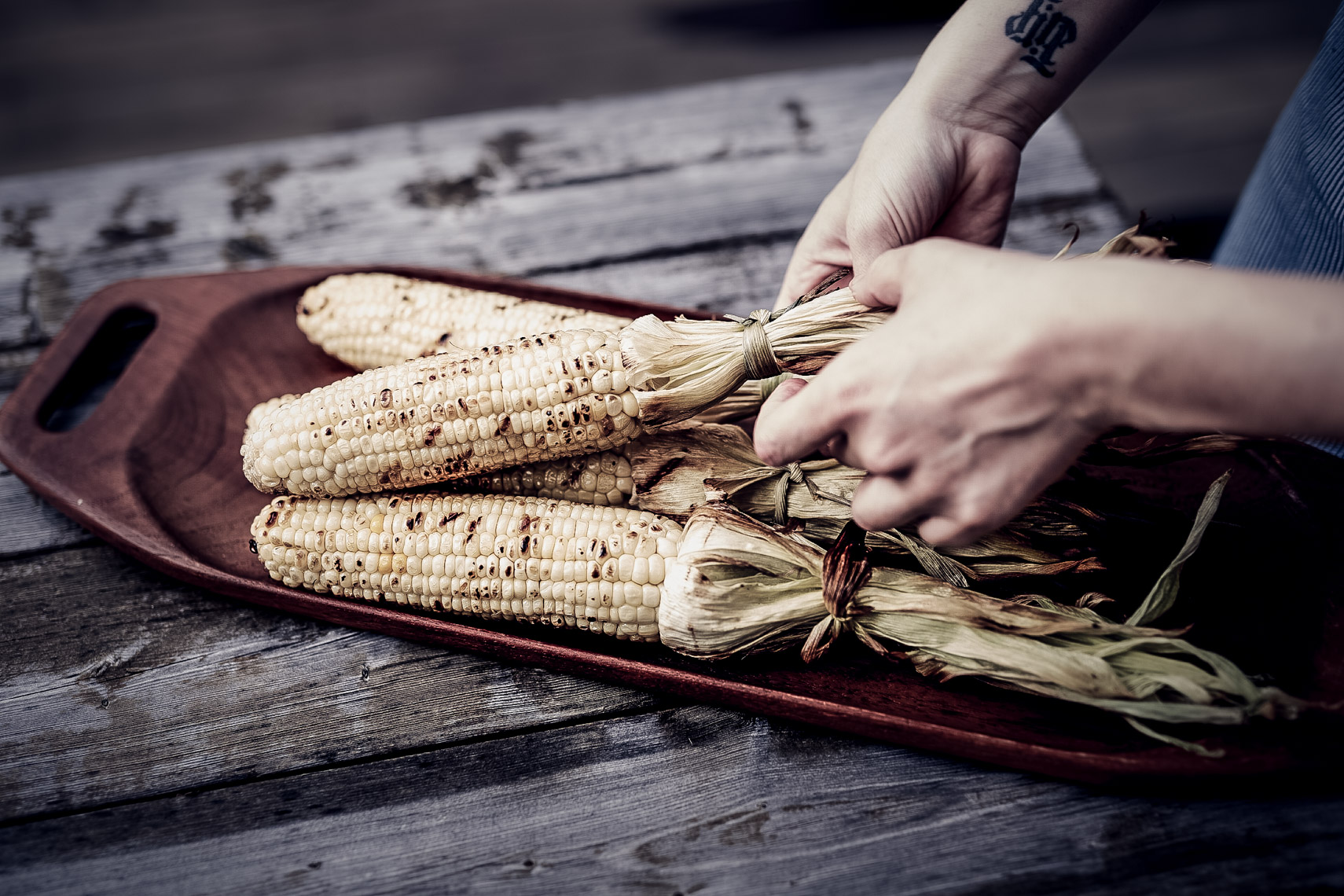 person husking grilled corn on wooden plate