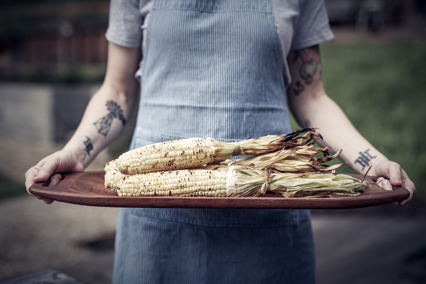 chef holding wooden tray of freshly grilled corn on the cob