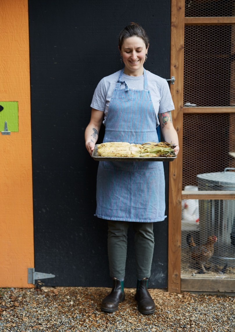 Woman in blue apron standing outside chicken coop holding a wood tray of corn on the cob