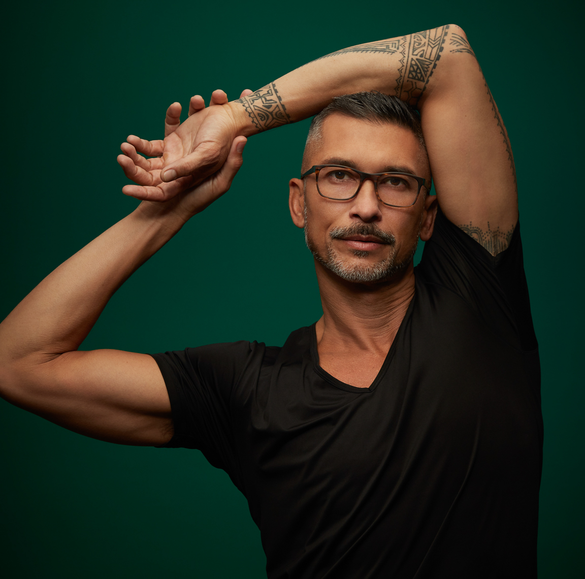 tatooed man with black t-shirtshort hair and elbo above his head hands clasped and glasses eyewear