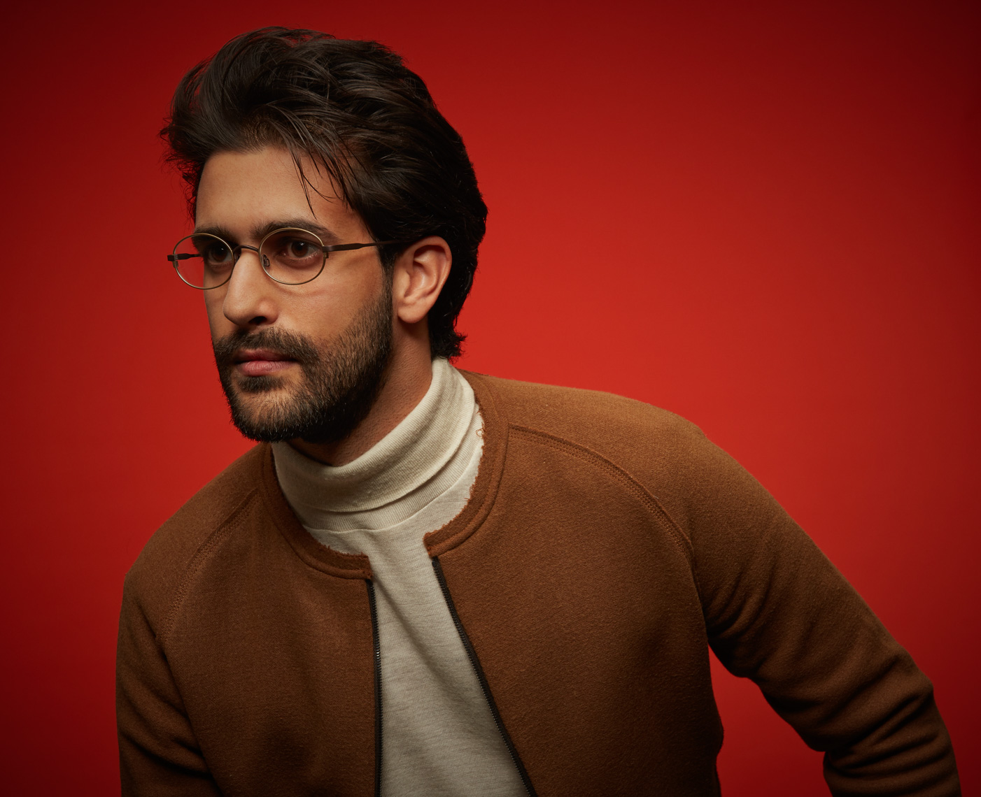 Dark haired man with beard and glasses wearing white turtleneck and camel jacket looking to the side