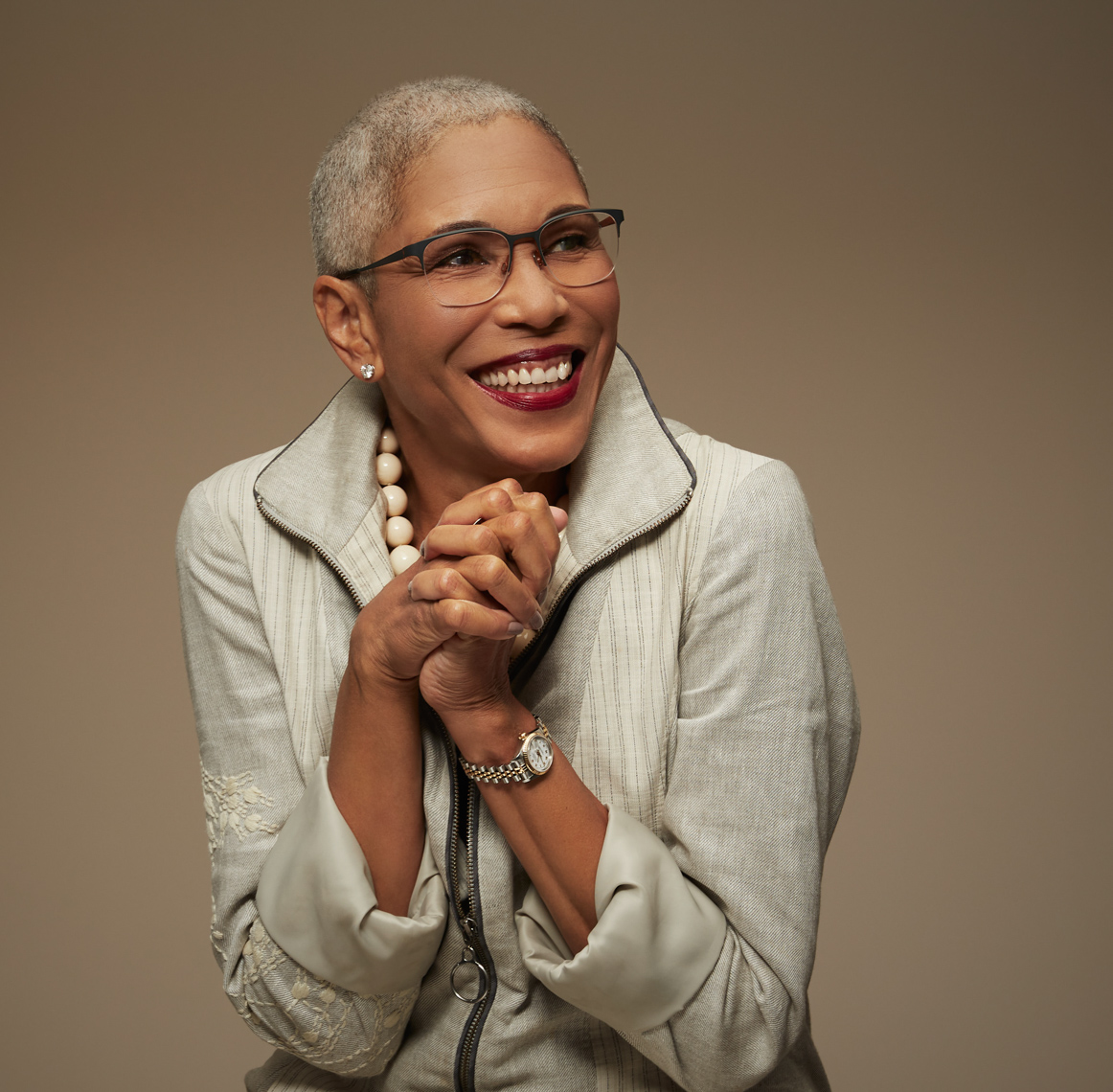 Silver haired woman in white jacket and pearls and glasses hands clasped with big smile and wearing glasses