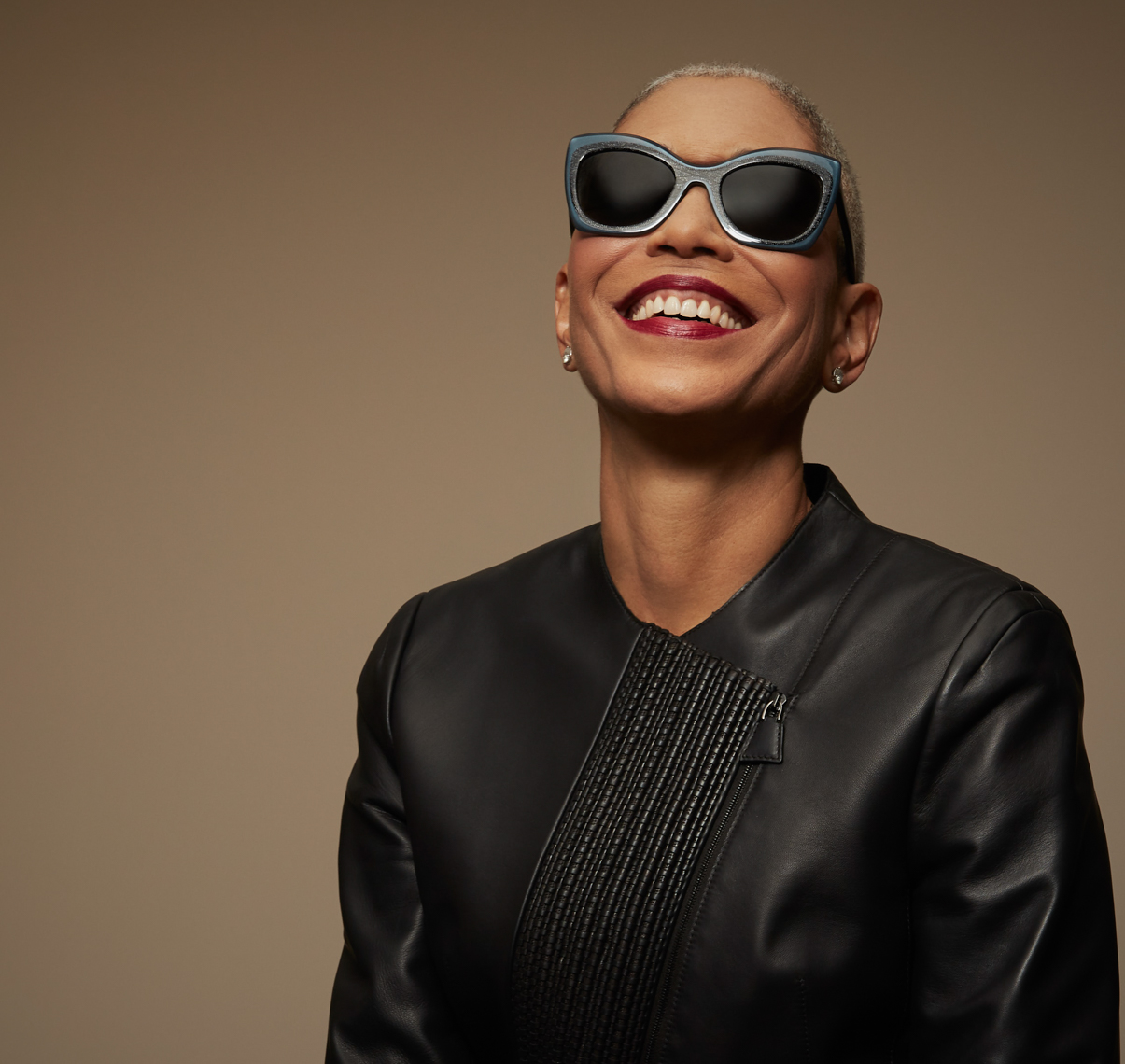 Silver haired woman in black leather jacket and glasses smiling and wearing sunglasses San Francisco fashion photographer