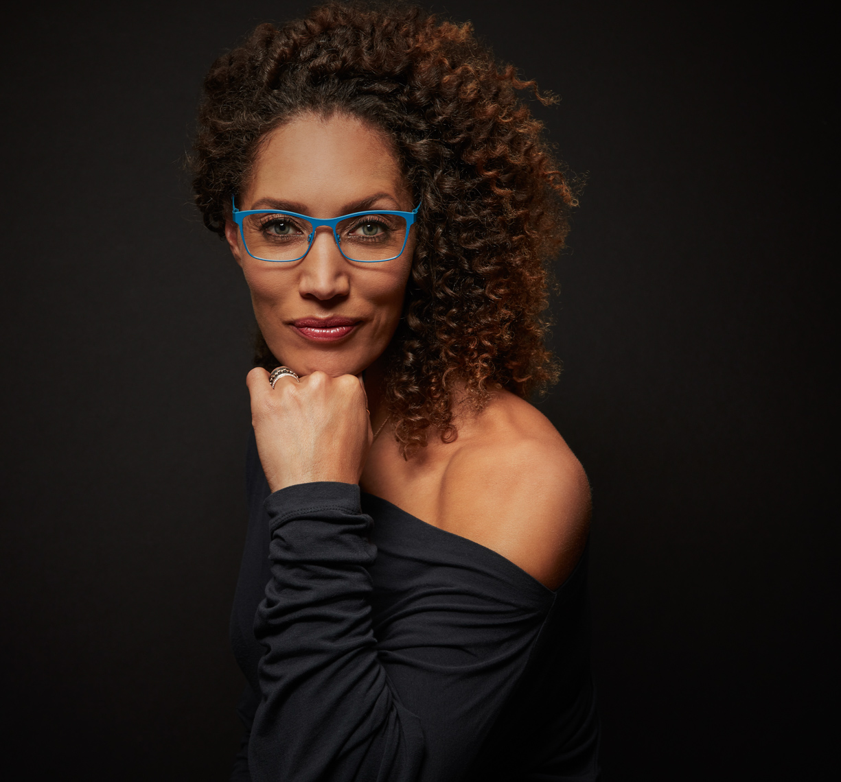 Woman with dark curly hair wearing black blouse with bare shoulder looking at camera with chin in hand and blue eyewear and black background San Francisco fashion photographer
