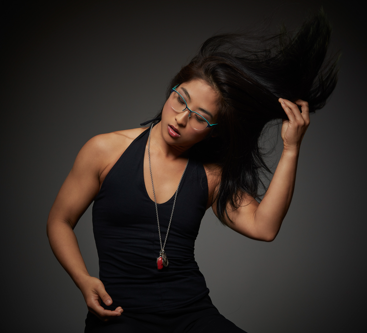 Asian woman flipping long dark hair wearing black low neck t-shirt and glasses San Francisco fashion photographer