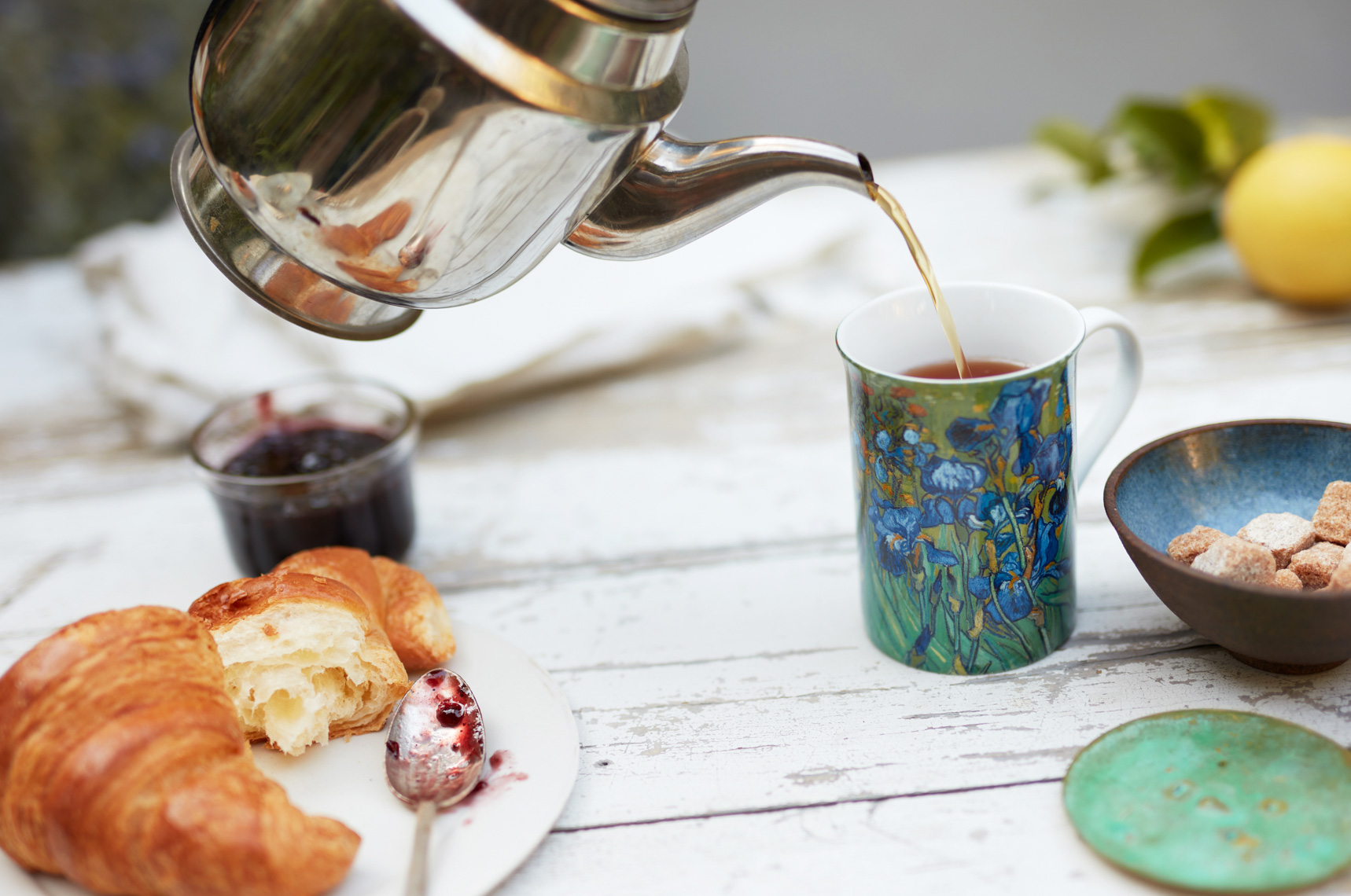 Silver teapot pouring tea into colorful mug with breakfast crescent and raw sugar