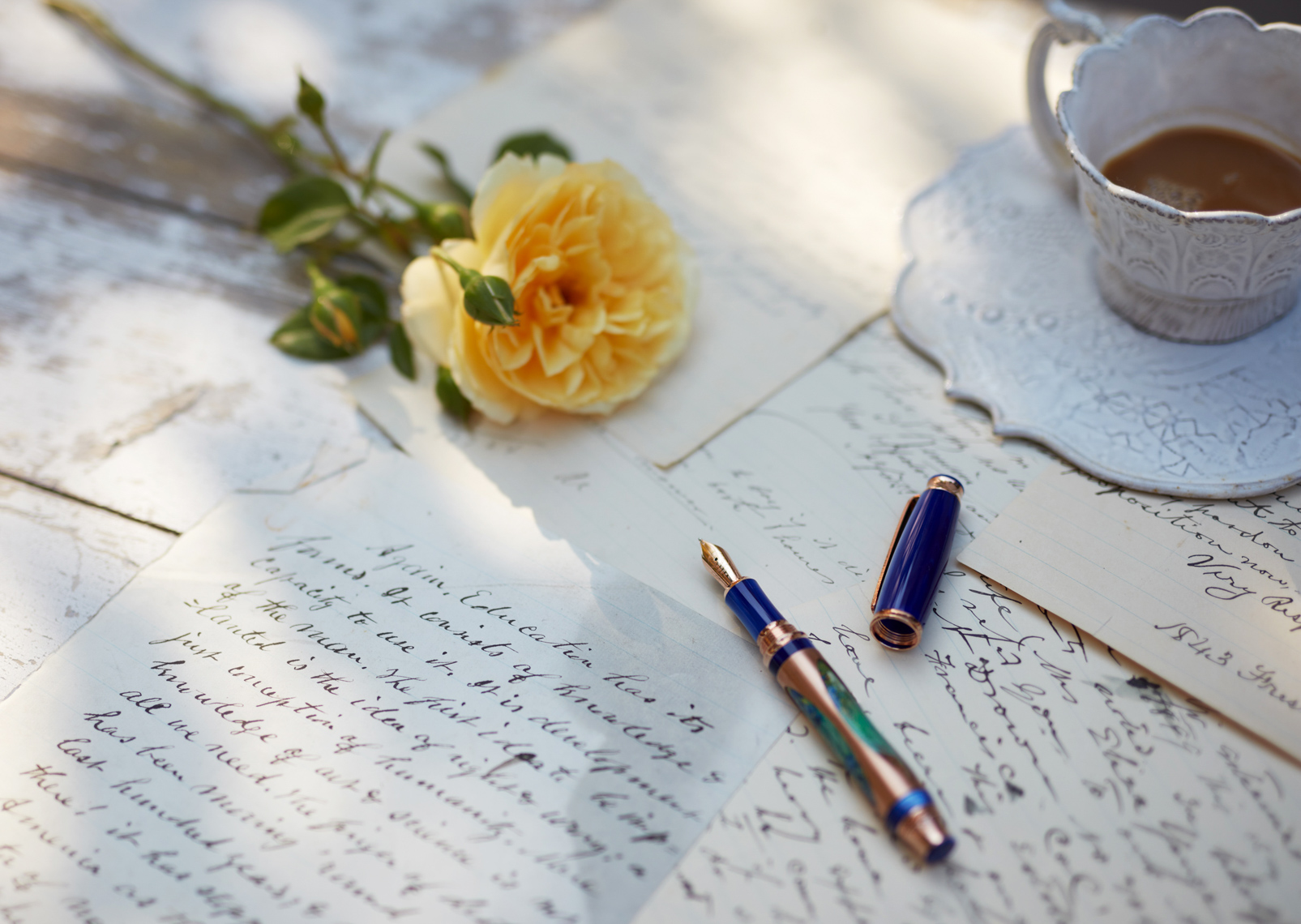 Old letters with colorful pen roses and tea