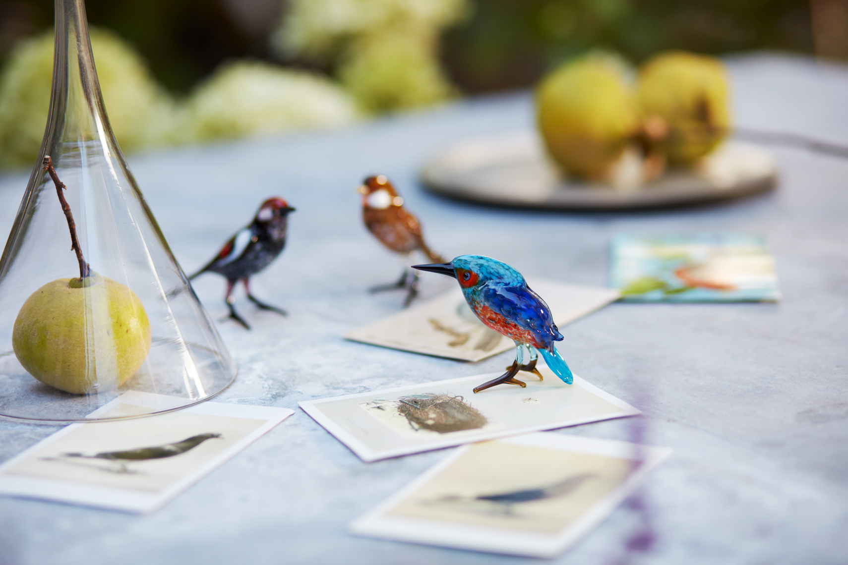 Glass bird ornaments with postcards and pears