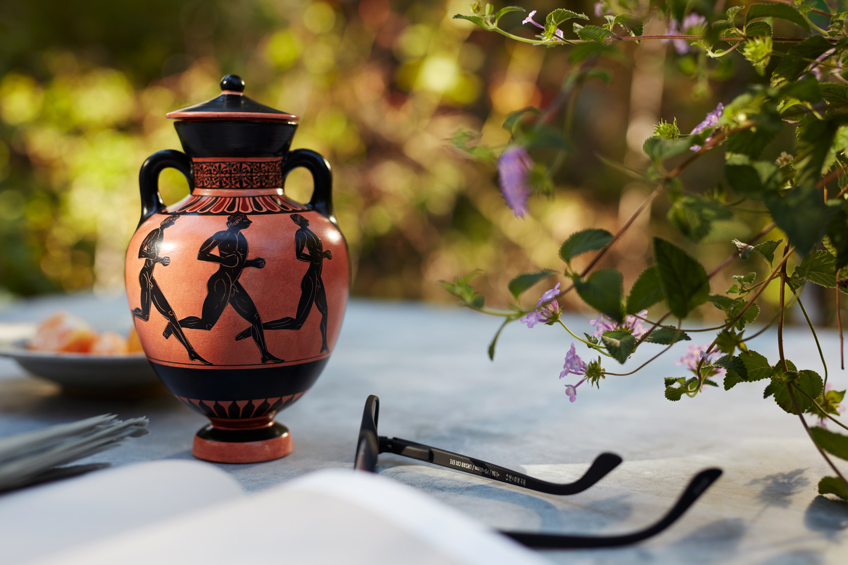 Grecian urn in garden with flowers and glasses