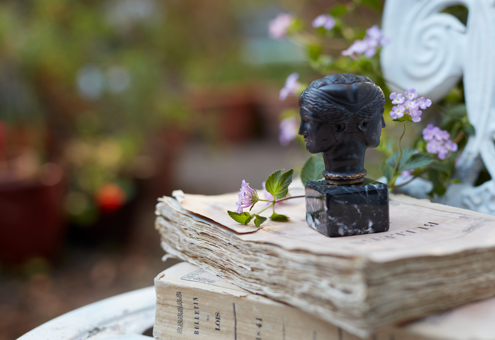 Ancient two-faced sculpture on old book in garden