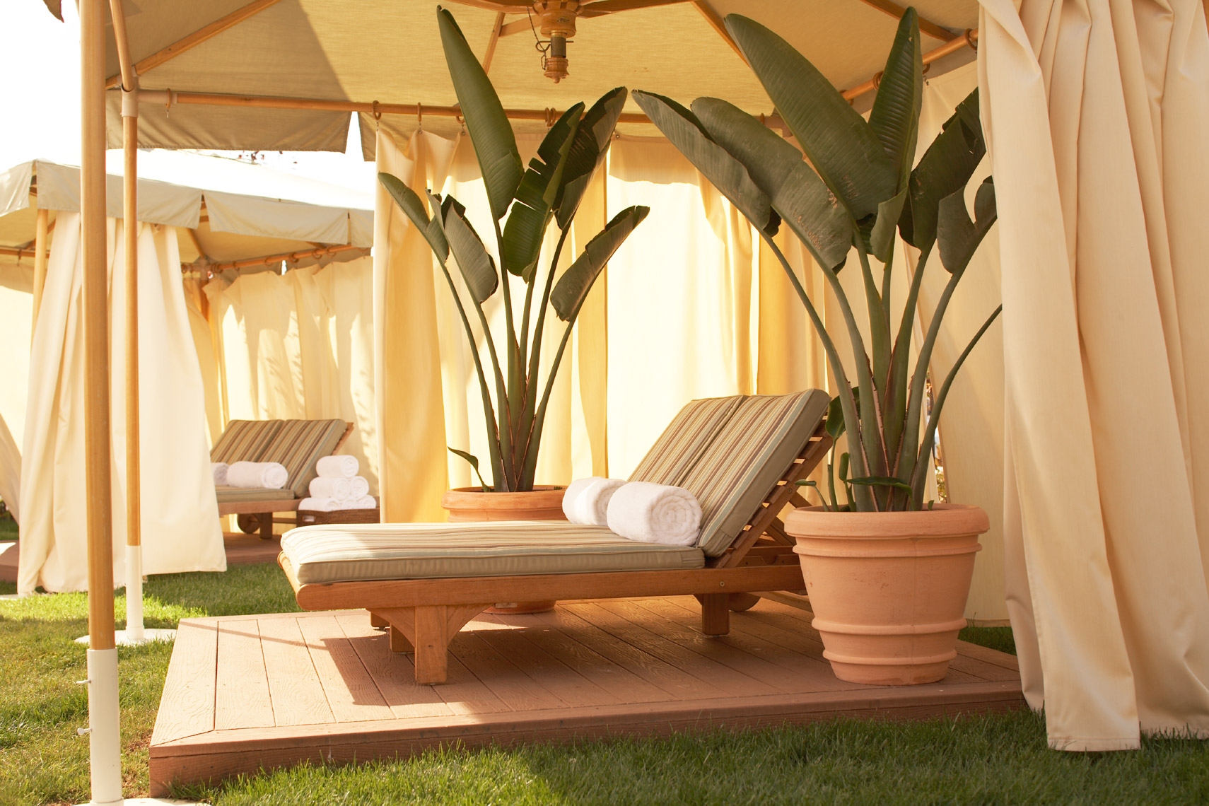 teak wooden patio lounge chaises with striped cushions and rolled white beach towels under canvas canopy at the resort spa San Francisco architectural photographer
