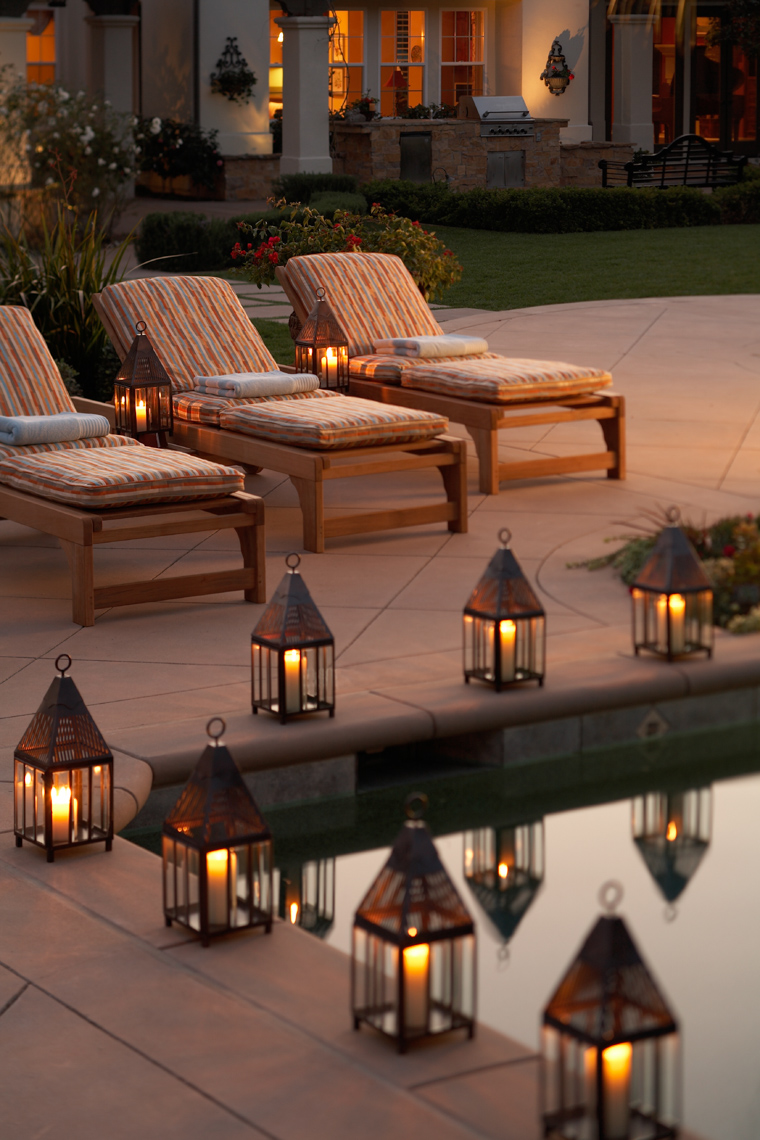 Lanterns and chaises on tile patio at dusk